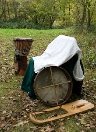 In a wooded clearing a bodhran, lyre and djembe stand around a chair covered with the Talesman's frock coat