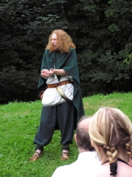 Wearing an iron age costume with a green cloak Talesman stands with cupped hands on a grassy bank before an audience