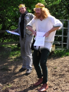 Longshanks and Talesman wearing carboard crowns and silly grins in a field whilst performing their feudal system sketch