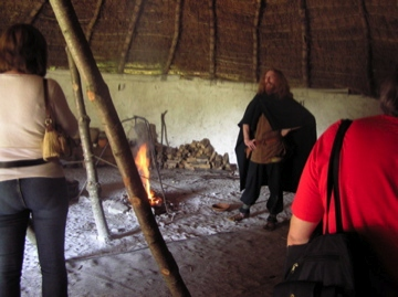 the inside of an iron age roundhouse with thatched roof, wattle and daub walls and the Talesman in full flow wering iron age clothes.