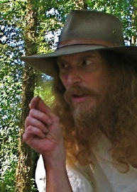 Wearing a wide brimmed hat in a sun dappled forest, the Talesman leans in closely